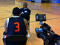 Basketball player and coach being interviewed on video
